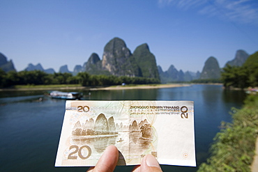 A tourist showing a RMB$20 note printed with the Guilin landscape as background, Xingping, Guilin, China