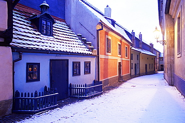 Snow covered 16th century cottages of Golden Lane (Zlata Ulicka) in winter twilight, Hradcany, Prague, Czech Republic, Europe