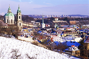 Snow covered Schonbornska Garden, Baroque St. Nicholas church and Mala Strana suburb rooftops in winter, Hradcany, Prague, Czech Republic, Europe
