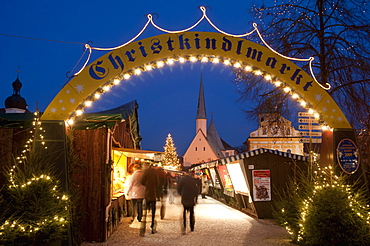 Sign over gate and stalls, Christmas Market (Christkindlmarkt) on Kapellplatz Square, at twilight, Altotting, Bavaria, Germany, Europe