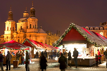Snow-covered Christmas Market and Baroque St. Nicholas Church, Old Town Square, Prague, Czech Republic, Europe