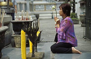 Thai Buddhist woman praying at temple, Wat Phra Kaew (Wat Phra Kaeo), Royal Palace, Bangkok, Thailand, Southeast Asia, Asia