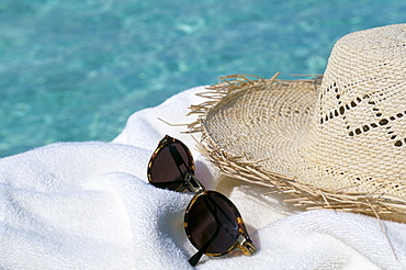 Straw hat and sunglasses on towel, North Male Atoll, Maldives, Indian Ocean, Asia