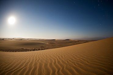 Moonrise over sand dunes, Skeleton Coast National Park, Namibia, Africa