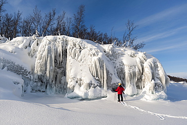 A woman looking at spectacular ice formations, Tornetrask Lake, Abisko National Park, Sweden, Scandinavia, Europe