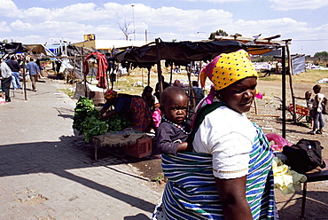 Woman carrying small child on her back, Soweto, Johannesburg, South Africa, Africa