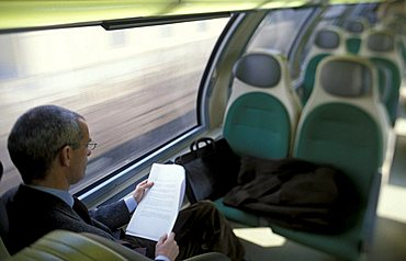 Businessman reading on train, Lombardy, Italy