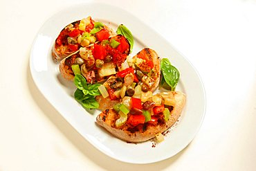 Caponata, sicilian dish made from aubergines, celery, olives, tomatoes, capers on toasted bread, Italy, Europe