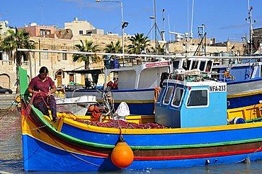 Woman at work on Luzzo traditional fishing boat, Marsaxlokk, Malta, Europe