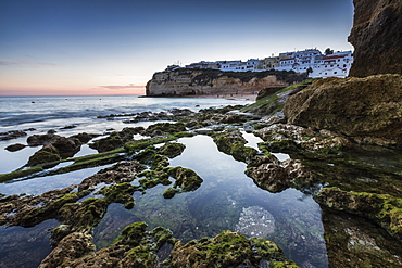 Sunset on the village perched on the promontory overlooking the beach of Carvoeiro, Algarve, Lagoa, Faro District, Portugal, Europe