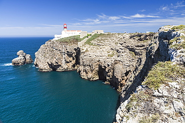 The cliffs and lighthouse overlooks the blue Atlantic ocean at Cabo De San Vicente, Sagres, Algarve, Portugal, Europe