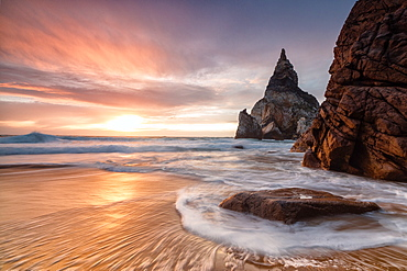 Golden reflections of the cliffs on Praia da Ursa beach bathed by ocean at sunset Cabo da Roca, Colares, Sintra, Portugal, Europe