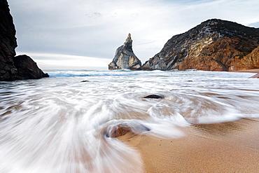Ocean waves crashing on the sandy beach of Praia da Ursa surrounded by cliffs, Cabo da Roca, Colares, Sintra, Portugal, Europe