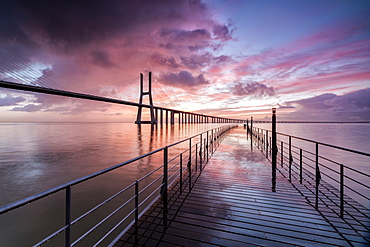 Sunrise colors the clouds reflected in Tagus River and frame the Vasco da Gama bridge in Lisbon, Estremadura, Portugal, Europe