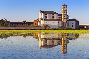 Abbey of Lucedio reflecting on rice fields at sunset, Trino Vercellese, Piedmont, Italy, Europe