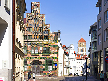 The Kerkhoffhaus buildt in the middle ages, church Nikolaikirche in the background. The hanseatic city of Rostock at the coast of the german baltic sea.  Europe,Germany, Mecklenburg-Western Pomerania, June