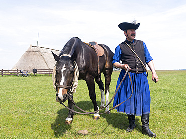Traditional hungarian cowboy show in the Hortobagy NP. Local cowboy / horseman or Csikos in traditional attire performing for tourists. Europe, Eastern Europe, Hungary, April