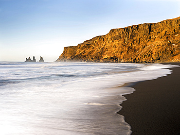 Coast of the North Atlantic near Vik y Myrdal during winter. Beach during sunrise with the sea stacks called Reynisdrangar. europe, northern europe, scandinavia, iceland,  February