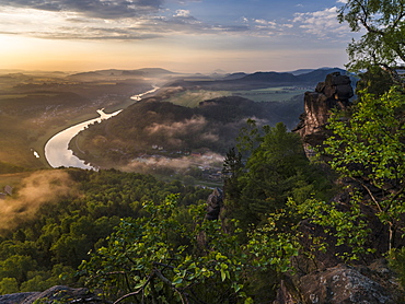 Elbe Sandstone Mountains (Elbsandsteingebirge) in the NP  Saxon Switzerland (Saechsische Schweiz) during spring. Valley of river Elbe with spa Bad Schandau during sunrise. Europe, Central Europe, Germany, Saxony, May