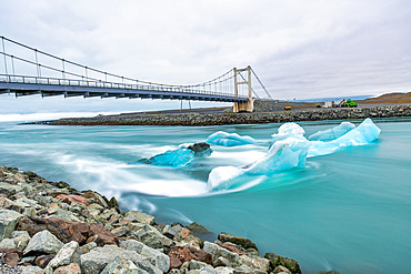 Jokulsarlon lake with icebergs at sunset, Iceland. Long exposure view with bridge on the background.