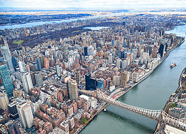 New York City from helicopter point of view. Queensboro Bridge with Manhattan skyscrapers on a cloudy day.