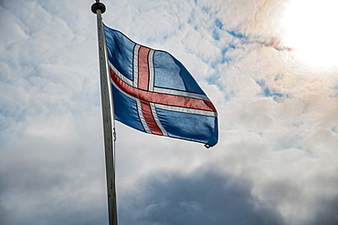 Waving flag of Iceland against sun and clouds