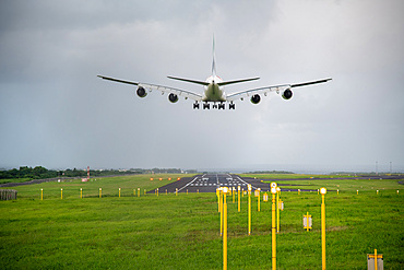 Giant aircraft landing at the airport with runway in the background. Back view.
