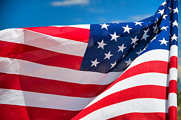 Waving American Flag on blue sky background.