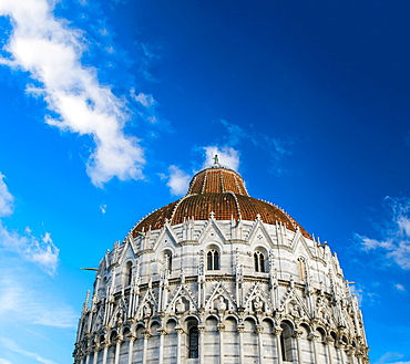 Pisa, Italy. Baptistery against the sky in famous Square of Miracles.