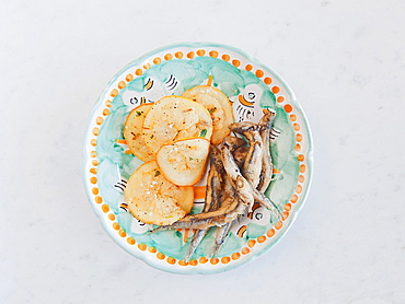 Fried anchovies and lemon in a plate of decaorated ceramic produced by Solimene in Vietri sul Mare village, Cetara, Amalfi coast, Campania, Italy, Europe