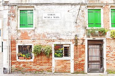 The front of an old house in Corte Scala Mata square, Cannaregio sestiere, not far from the Jewish ghetto in Venice, Veneto, Italy, Europe