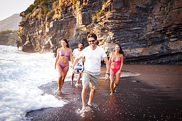 Group of smiling boys and girls on the Black Beach of Maratea at sunset, Basilicata, Italy, Europe