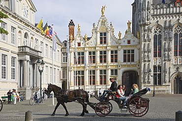 A horse drawn carriage crosses the Burg Square, passing the Stadhuis (Town Hall) buildings, Brugge, Belgium, Europe