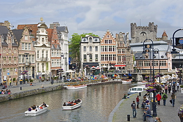 Everyday scene along the Graslei bank, lined with Baroque style Flemish gabled houses, Gravensteen Castle beyond, in the centre of Ghent, Belgium, Europe