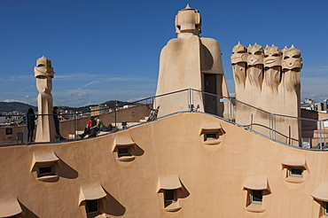 Group of four grotesque chimneys on the roof of La Pedrera (Casa Mila), and roof window details on an apartment block designed by Antonio Gaudi, UNESCO World Heritage Site, Passeig de Gracia, Barcelona, Catalunya, Spain, Europe