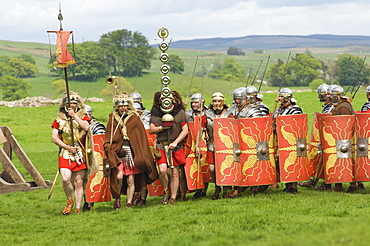 Roman soldiers of the Ermine Street Guard, marching in column led by Standard Bearers and Trumpeter, Birdoswald Roman Fort, Hadrians Wall, Northumbria, England, United Kingdom, Euruope