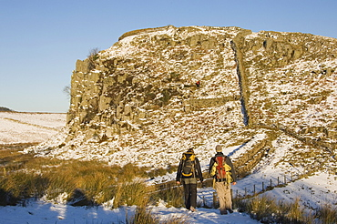 Two climbers head for the crags at Steel Rigg, Hadrians Wall, UNESCO World Heritage Site, Northumbria, England, United Kingdom, Europe