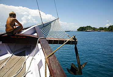 Tourist on a schooner cruising between the different beaches and islands around Paraty (Parati), Rio de Janeiro State, Brazil, South America
