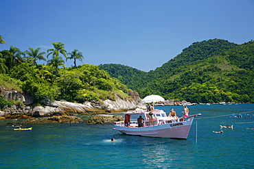 Tourist on a chartered fishing boat cruising between the different beaches and islands around Paraty (Parati), Rio de Janeiro State, Brazil, South America