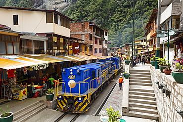 Train crossing the town of Aguas Calientes, Peru, South America