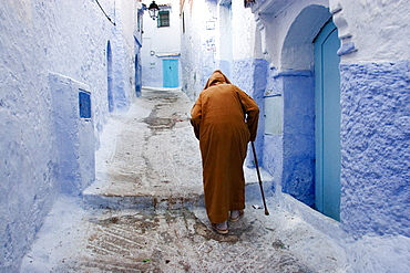 Old man walking in a typical street in Chefchaouen, Rif mountains region, Morocco, North Africa, Africa
