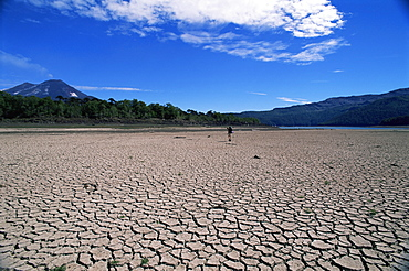 Backpacker walking across dried up lake towards Llaima volcano, Conguillio National Park, Chile, South America