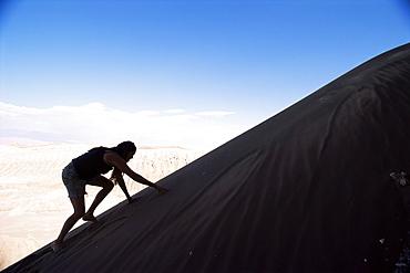 Tourist climbing dunes, Valle de la Luna (Valley of the Moon) (Moon Valley), Atacama Desert, Chile, South America