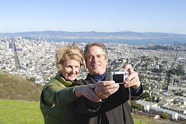 Married couple take photo of themselves, with downtown San Francisco beyond, California, United States of America, North America