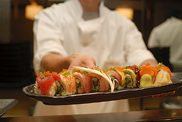 Sushi chef presents a plate of various seafood sushi, Japan, Asia