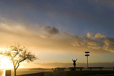 Silhouette of girl stretching at sunset, Puget Sound, with Blake Island in distance, Upper Queen Anne, Seattle, Washington. United States of America, North America