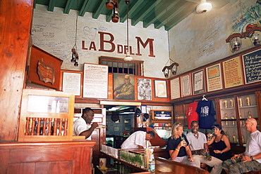 Tourists enjoy mojitos at the Bodegita del Medio, one of Havana's oldest bars, where the first mojito was made, and a favourite hangout of Ernest Hemingway, Havana, Cuba, West Indies, Central America