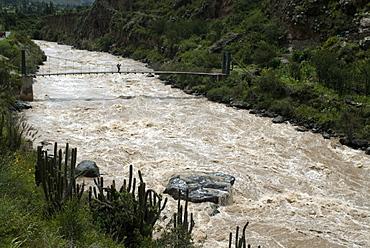 Backpacker crosses bridge over Urubamba River, on the Inca Trail, Peru, South America