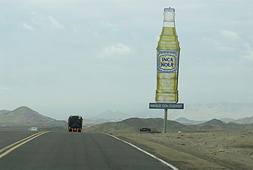Transport truck on the Pan American highway in northern Peru, South AmericaInca Kola (The National Soda) sign on the side of the road