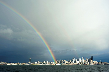 A rainbow lands on a Washington State Ferry in the Puget Sound with the Seattle skyline in the background, Seattle, Washington, United States of America, North America